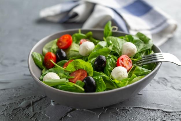 Frisse salade met mozzarellakaas, tomaat en spinazie. gezond dieetvoeding.