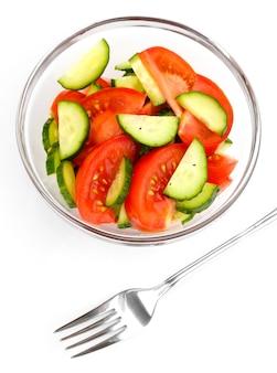 Frisse salade met tomaten en komkommers op wit