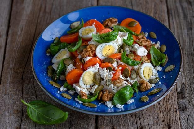 Frisse salade met wortelen en kwarteleitjes. vegetarische salade. goede voeding. gezond eten voor de lunch. zakenlunch. salade met noten en basilicumblaadjes.