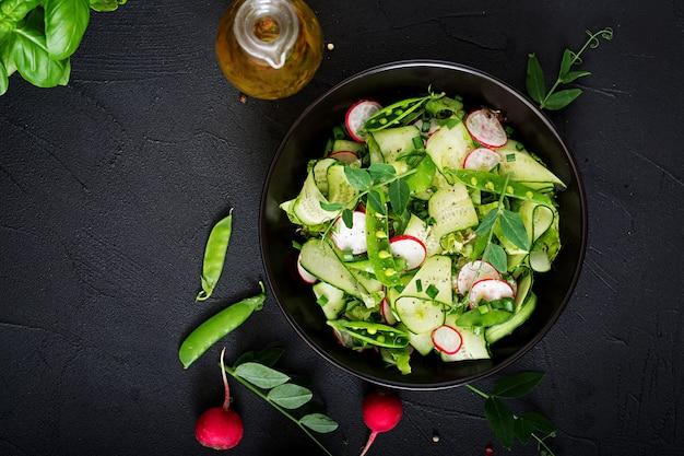 Frisse salade van komkommers, radijsjes, doperwtjes en kruiden. plat liggen. bovenaanzicht