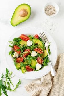 Frisse salade van rucola, tomaat, avocado, olijfolie, noten en kwarteleitjes op een lichte stenen achtergrond