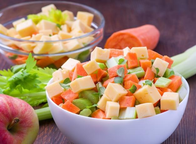 Frisse salade van stengels bleekselderij, wortelen, appels en kaas