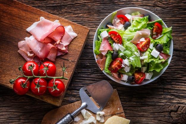 Frisse slasaladegezonde mediterrane salade olijven tomaten parmezaanse kaas en prosciutto