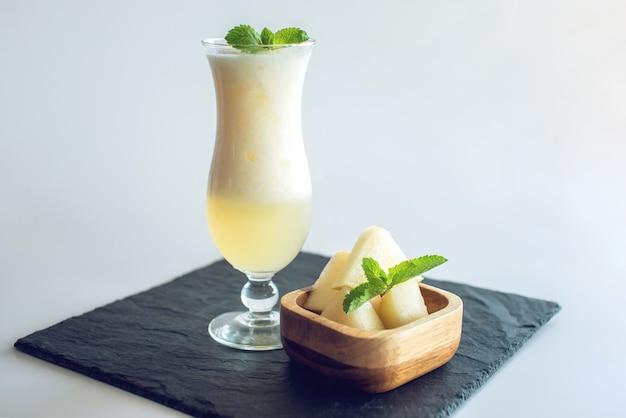Frisse witte smoothie in een glas met gesneden stukjes meloen en munt