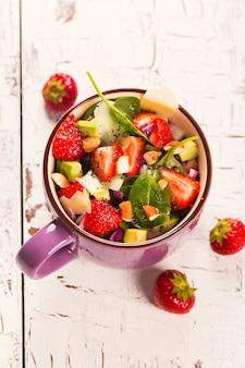 Frisse zomer salade met aardbei, avocado en spinazie op witte rustieke houten achtergrond. bovenaanzicht