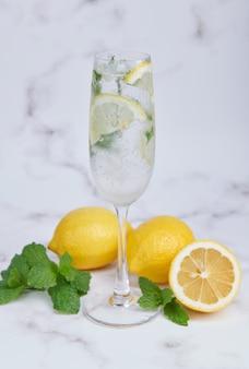 Frisse zomercocktail met citroenen, munt en ijs, selectieve focusafbeelding, mojito in een glazen beker, verse citruslimonade met limoenen en citroenen. frisse en koele drank voor het zomerconcept.
