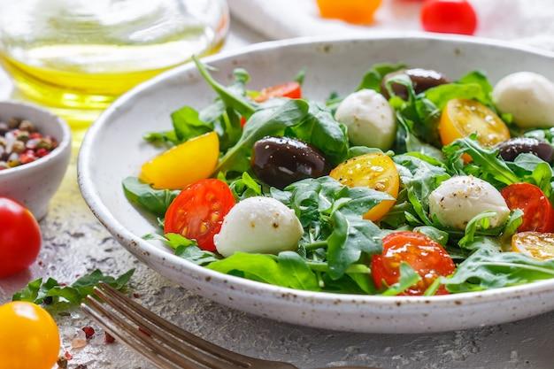 Frisse zomersalade met rucola, gele en rode kerstomaten, kalamata-olijven en mozzarella