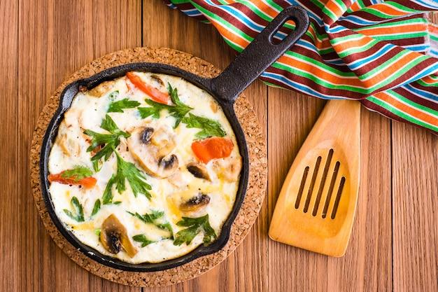 Frittata gemaakt van eieren, kip, champignons, uien, tomaten, kaas en peterselie in ijzeren pan. bovenaanzicht