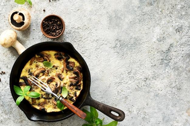Frittata met champignons in een pan met basilicum op een betonnen achtergrond. fritata is een italiaans ontbijtgerecht.