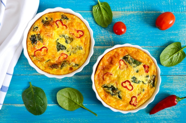 Frittata met verse groenten en spinazie. italiaanse omelet in keramische vormen op een blauwe houten achtergrond. bovenaanzicht.