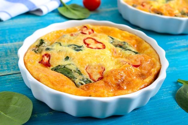 Frittata met verse groenten en spinazie. italiaanse omelet in keramische vormen op een blauwe houten achtergrond.