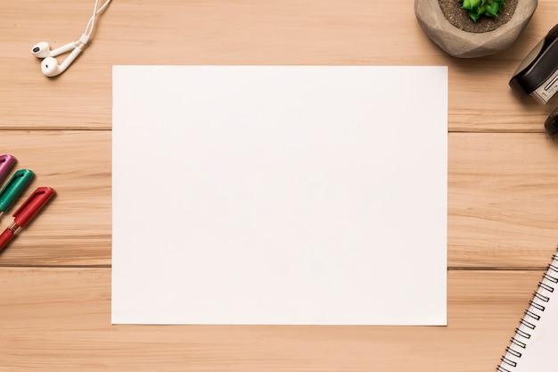 Frome hierboven van blanco vel papier omringd door kantoorbenodigdheden