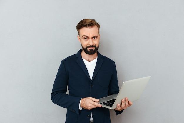 Frons ernstige mens in kostuum dat geïsoleerde laptop met behulp van