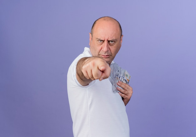 Fronsen casual volwassen zakenman staande in profiel weergave geld houden en wijzend op camera geïsoleerd op paarse achtergrond met kopie ruimte