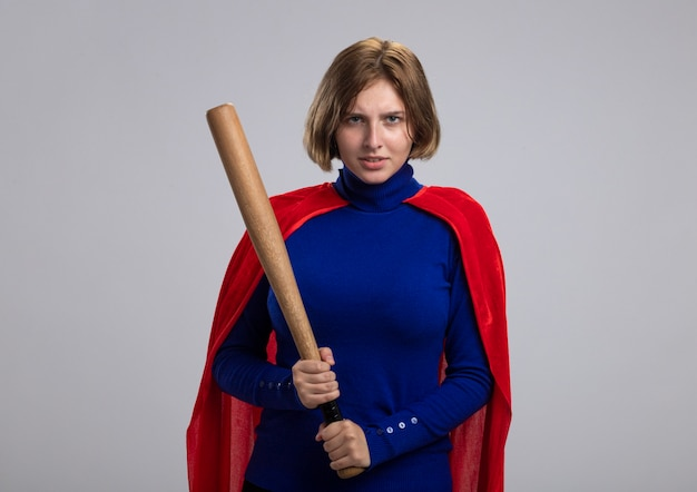 Fronsen jong blonde superheld meisje in rode cape met honkbalknuppel geïsoleerd op een witte muur met kopie ruimte