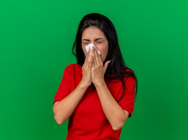 Fronsen jong kaukasisch ziek meisje neus afvegen met servet met gesloten ogen geïsoleerd op groene muur met kopie ruimte