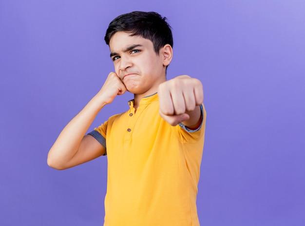 Fronsen jonge blanke jongen aanraken van gezicht met vuist uitrekkende vuist naar geïsoleerd op paarse muur met kopie ruimte