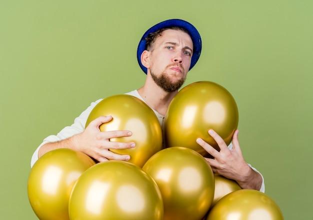 Fronsen jonge knappe feestman met feestmuts achter ballonnen grijpen hen kijken naar voorzijde geïsoleerd op olijfgroene muur