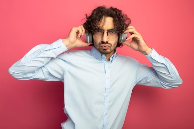 Fronsen jonge knappe man met bril en koptelefoon kijken naar voorzijde grijpende koptelefoon geïsoleerd op roze muur