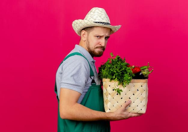 Fronsen jonge knappe slavische tuinman in uniform en hoed staande in profiel te bekijken op zoek mand met groenten