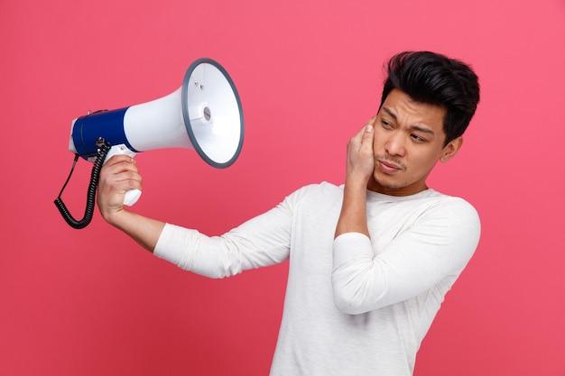 Fronsen jonge man houden hand op oor houden spreker kant kijken Gratis Foto