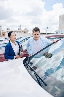 Fronsen jonge man kijken naar auto's in autodealer met hulp van manager