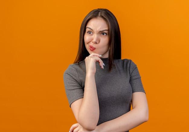 Fronsen jonge mooie vrouw handen onder de elleboog en op de kin kijken kant geïsoleerd op een oranje achtergrond met kopie ruimte