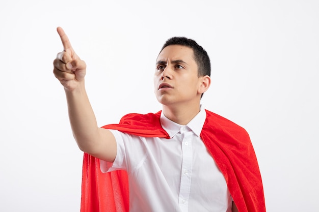 Fronsen jonge superheld jongen in rode cape kijken en wijzend naar kant geïsoleerd op een witte achtergrond