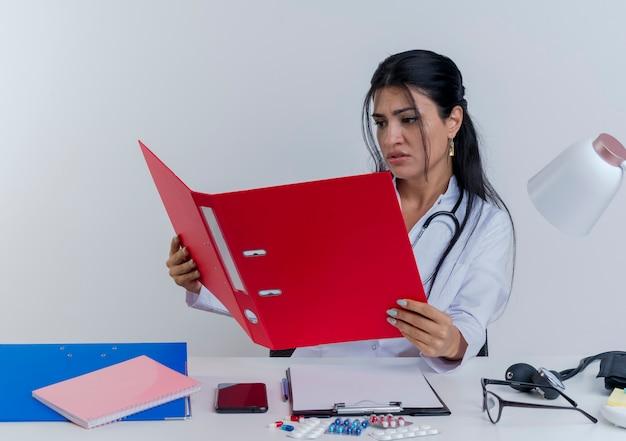 Fronsen jonge vrouwelijke arts die medische mantel en stethoscoop zittend aan een bureau met medische hulpmiddelen houden en kijken naar geïsoleerde map
