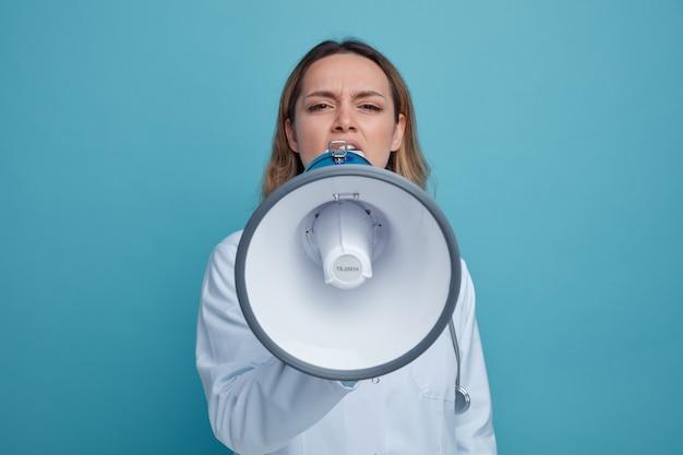 Fronsen jonge vrouwelijke arts medische gewaad en stethoscoop dragen om nek praten door spreker