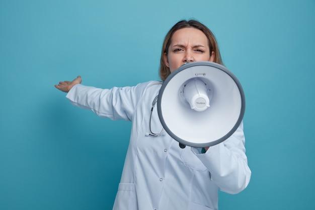 Fronsen jonge vrouwelijke arts medische gewaad en stethoscoop dragen rond de nek praten door spreker achter met de hand te wijzen