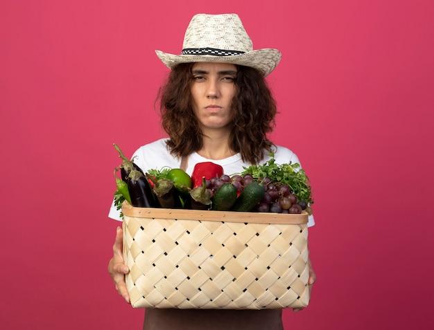 Fronsen jonge vrouwelijke tuinman in uniform dragen tuinieren hoed met plantaardige mand