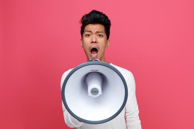 Fronsen jongeman schreeuwen in luidspreker