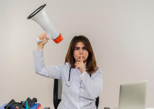 Fronsen middelbare leeftijd vrouwelijke arts dragen medische gewaad en stethoscoop zit aan bureau met medische hulpmiddelen klembord en laptop verhogen spreker doet stilte gebaar geïsoleerd