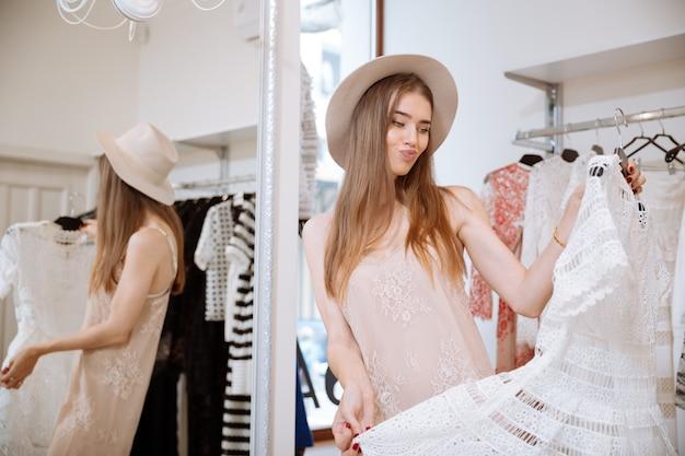 Fronsen teleurgestelde jonge vrouw in hoed die het winkelen doet en kleding in kledingwinkel kiest