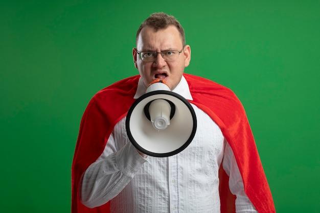 Fronsen volwassen superheld man in rode cape bril kijken voorzijde praten door spreker geïsoleerd op groene muur