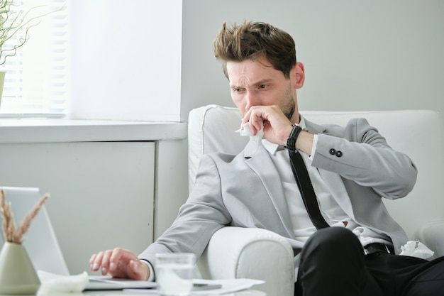 Fronsen zieke jonge zakenman zittend in een stoel en werken aan project met behulp van laptop terwijl het koud is