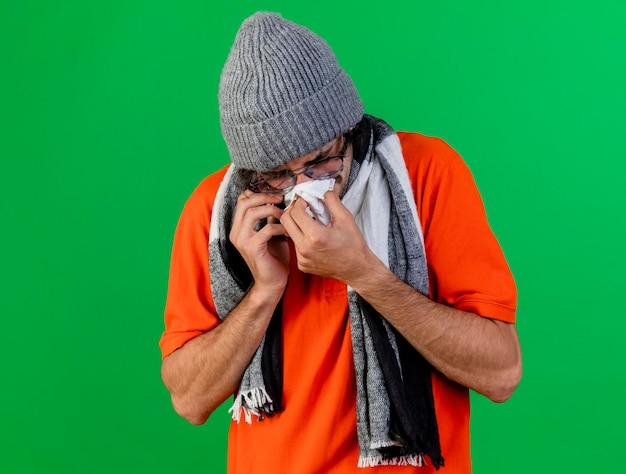 Fronsen zieke jongeman bril winter muts en sjaal praten over telefoon neus afvegen met servet met gesloten ogen geïsoleerd op groene muur met kopie ruimte