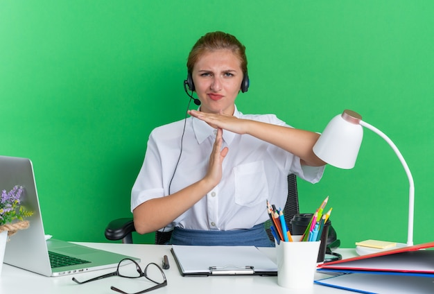 Fronsend jong blond callcentermeisje met een hoofdtelefoon die aan het bureau zit met uitrustingsstukken die een time-outgebaar doen