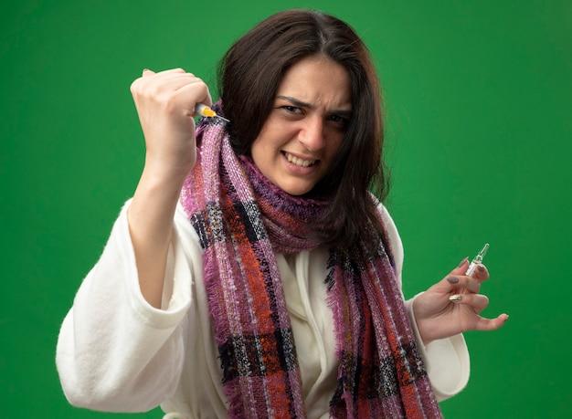 Fronsend jong kaukasisch ziek meisje dat gewaad en sjaal draagt die ampul houdt en spuit uitrekt die op groene muur wordt geïsoleerd