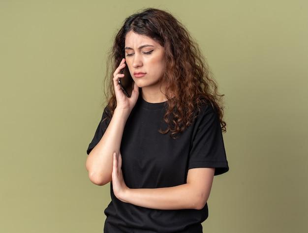 Fronsend jong mooi meisje dat aan de telefoon praat en neerkijkt op een olijfgroene muur met kopieerruimte