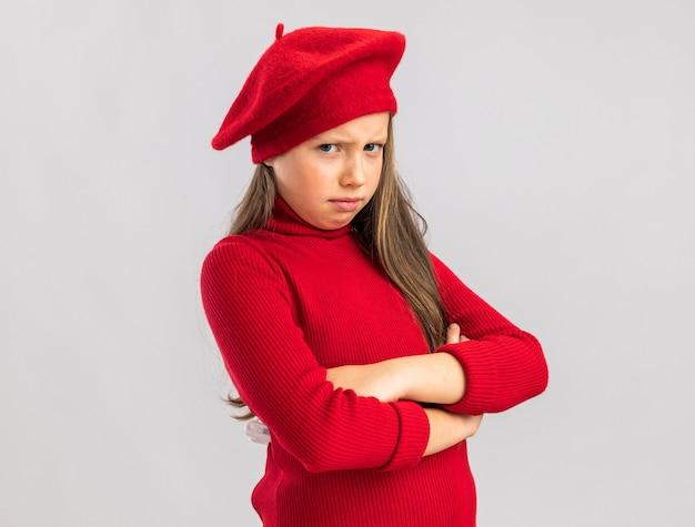 Fronsend klein blond meisje met een rode baret die de armen gekruist houdt en naar de voorkant kijkt geïsoleerd op een witte muur met kopieerruimte