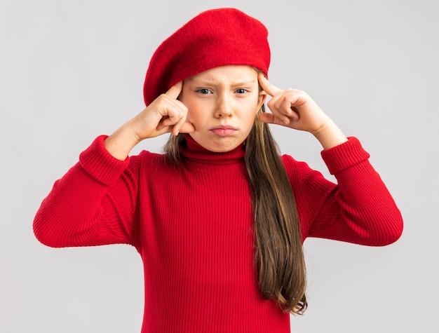 Fronsend klein blond meisje met een rode baret die naar de camera kijkt en een denkgebaar doet dat op een witte muur wordt geïsoleerd