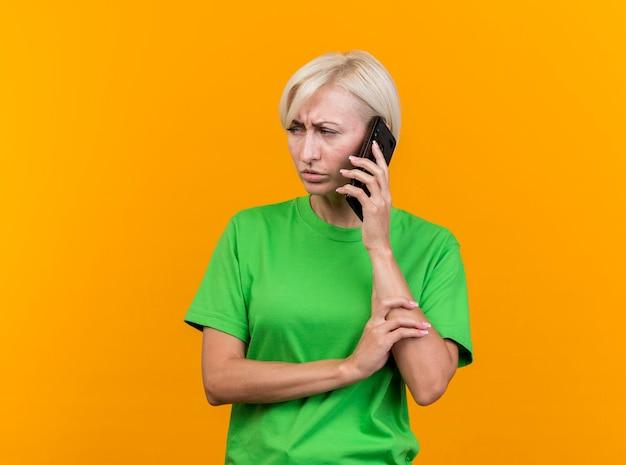 Fronsende blonde slavische vrouw van middelbare leeftijd die op de arm van de telefoonholding spreekt die kant bekijkt die op gele muur met exemplaarruimte wordt geïsoleerd
