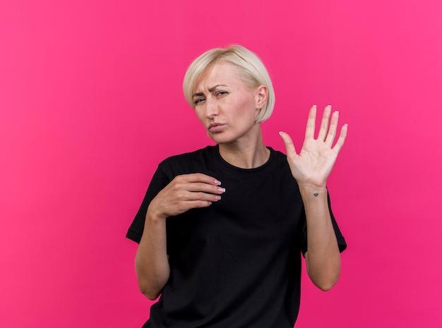 Fronsende blonde slavische vrouw van middelbare leeftijd kijken naar voorkant met vijf met hand houden van een andere in de lucht geïsoleerd op roze muur met kopie ruimte