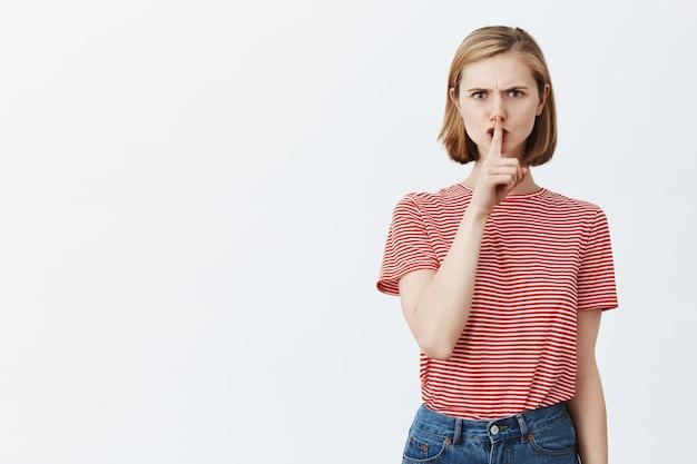 Fronsende boze vrouw die uitscheldt omdat ze verkeerd handelt, zwijgend naar je