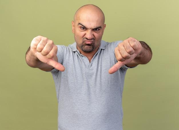 Fronsende casual man van middelbare leeftijd met duimen naar beneden geïsoleerd op olijfgroene muur