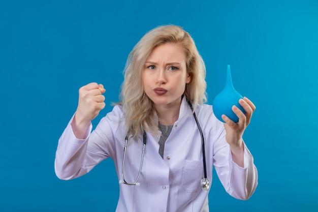 Fronsende jonge arts die stethoscoop in medische toga draagt die klysma op blauwe muur houdt
