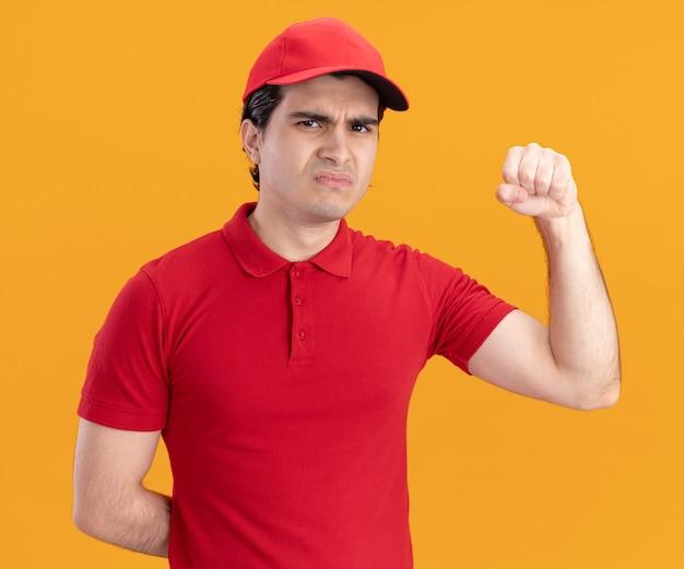 Fronsende jonge bezorger in blauw uniform en pet die de hand achter de rug houdt en naar de voorkant kijkt met een kloppend gebaar geïsoleerd op een oranje muur