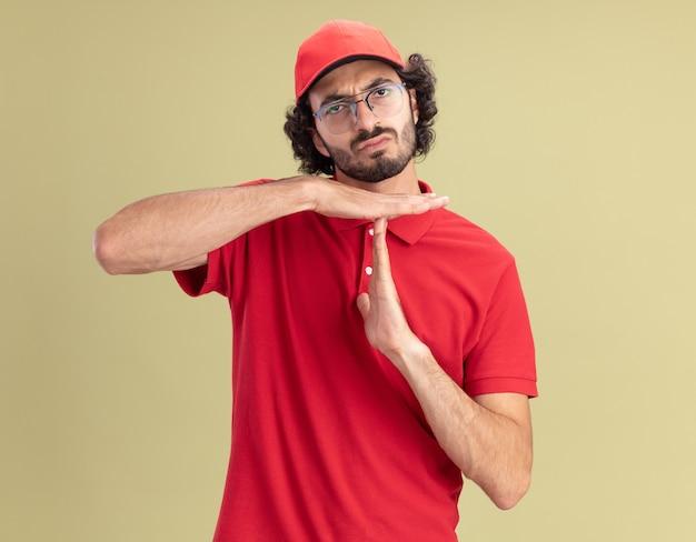 Fronsende jonge bezorger in rood uniform en pet met een bril die naar de voorkant kijkt en een time-outgebaar doet dat op een olijfgroene muur wordt geïsoleerd